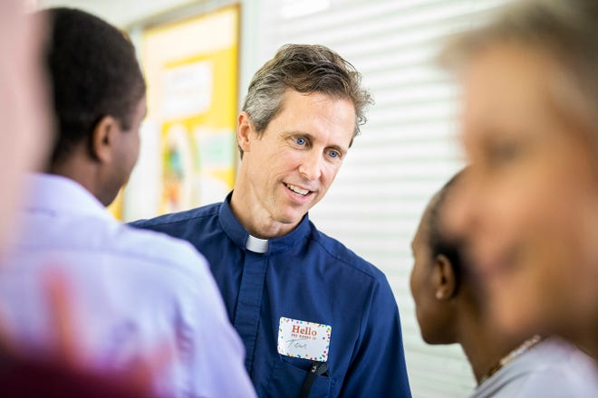 The Rev. Tom Holdcraft speaks to St. Stephen Lutheran Church members Eunice and Victor Muchuruza in June, when he was invited to meet the people of his prospective new congregation.