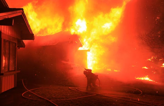 In this Oct. 9, 2017, file photo, Cazadero firefighter struggles to protect a home from catching fire in Coffey Park, in Santa Rosa.