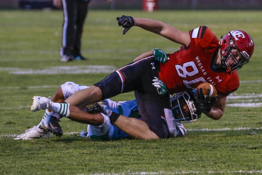 East's Caleb Gruszynskii is brought down by  Rhinelander's Josh Francisco after a catch during the first half of the Lumberjacks matchup with Rhinelander on Thursday.