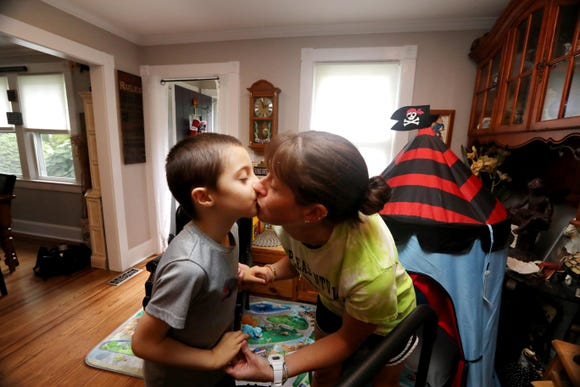 Kristen Coffey, head coach of the Pleasantville High School varsity field hockey team, gets a kiss from her 6-year-old autistic son Peyton at their home in Pleasantville Aug. 31, 2018. Coffey has organized a field hockey tournament to benefit the autism advocacy organization Autism Speaks. The tournament will take place Sept. 8, 2018, at Pleasantville High School.