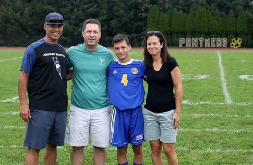 Ardsley boys soccer coach Eric Petrone, poses with David, Matthew and Jennifer Halperin before their boys soccer game against New Rochelle at Ardsley High School, Aug. 31, 2018. Matthew's brother Harris, who would have been a senior and a captain, passed away from cancer and the team has made his younger brother an honorary captain.