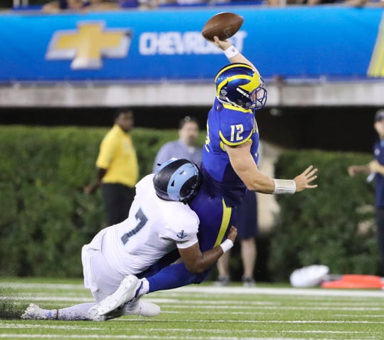 Delaware's Pat Kehoe unloads the ball as he is dragged down by Rhode Island's L.B. Mack III in the third quarter of the Blue Hens' 21-19 loss at Delaware Stadium Thursday.