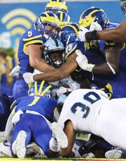 Delaware's Charles Bell (5), Malcolm Brown (1) and Armen Ware converge on Rhode Island's Zoe Bryant in the first half at Delaware Stadium Thursday.