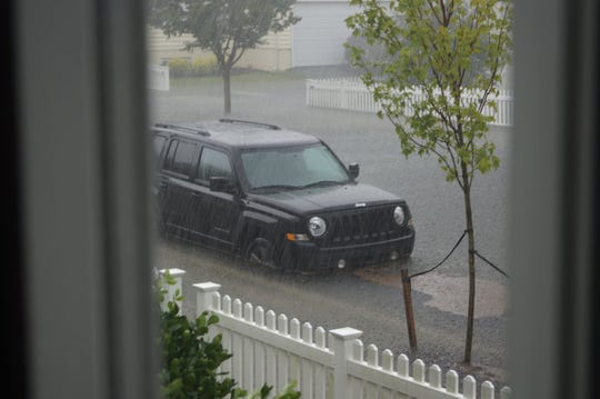 A vehicle is partially submerged in floodwaters Friday in Milton's neighborhood of Cannery Village.