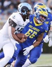 Rhode Island quarterback JaJuan Lawson tries to evade Delaware's Caleb Ashworth in the first quarter at Delaware Stadium Thursday.