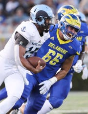 Rhode Island quarterback JaJuan Lawson tries to evade Delaware's Caleb Ashworth in the first quarter at Delaware Stadium Thursday, Aug. 30, 2018.