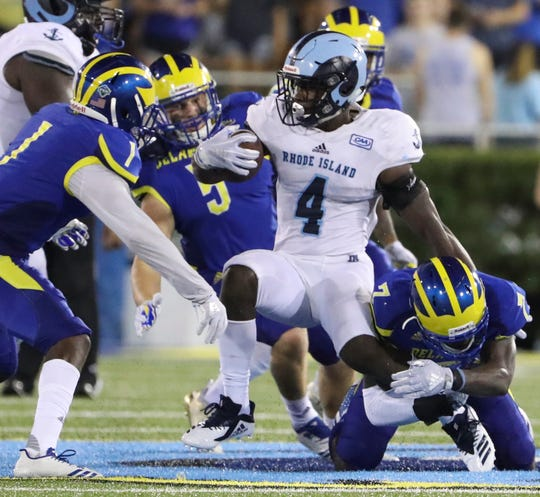 Delaware's (from left) Malcolm Brown, Charles Bell and Ray Jones bring down Rhode Island's Zoe Bryant in the fourth quarter of the Blue Hens' 21-19 loss at Delaware Stadium Thursday.