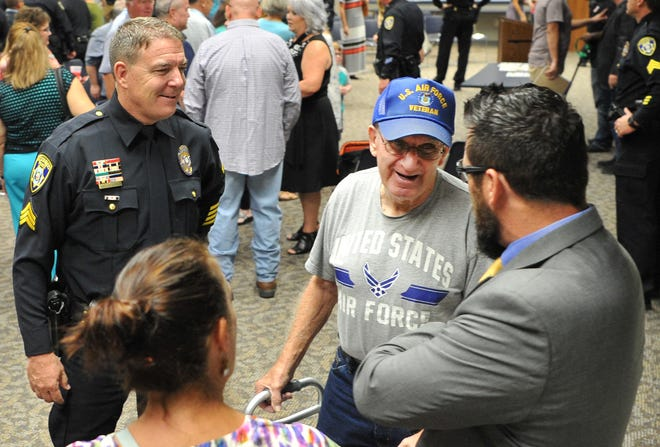 Wichita Falls Police Sergeant, Charlie Eipper, left, and Sergeant Jonathan Lindsey, right,  talk with, Walter Cummins, centered, a man they helped after collapsing from a major heart attack while attending church at Grace Church in Wichita Falls. Eipper and Lindsey were awarded the department's Life-Saving Bar for their actions during a Retirement, Promotion, and Award Ceremony Friday morning.