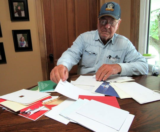 Bob selects a winner from a pile of Christmas cards sent in by Wisconsin State Farmer readers.