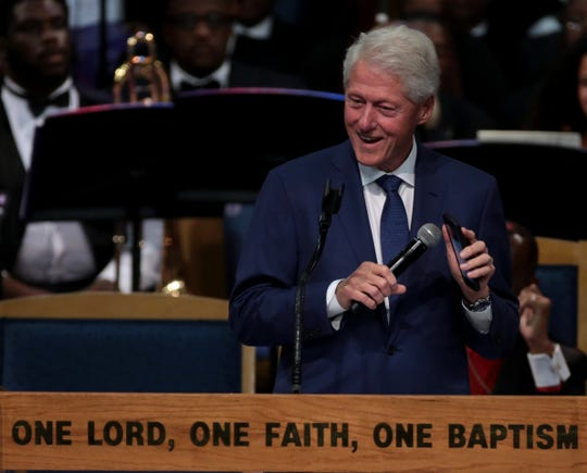 "Former president Bill Clinton plays ""Think"" by Aretha Franklin on his phone during his speech at her funeral."