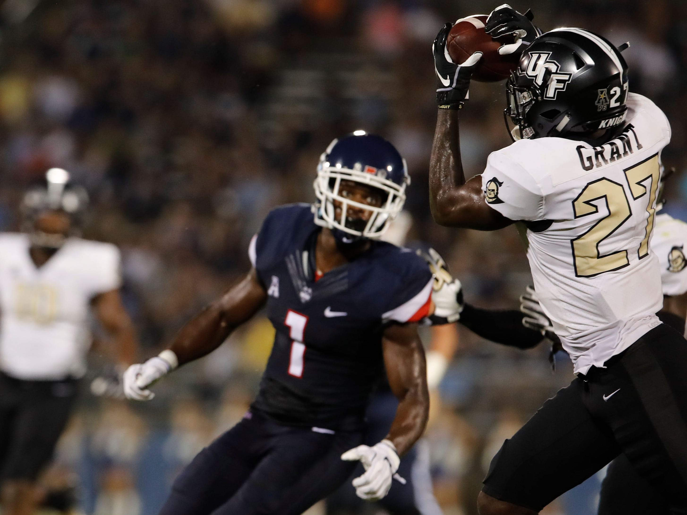 UCF defensive back Richie Grant intercepts a pass intended for Connecticut wide receiver Hergy Mayala (1) in the second quarter at Pratt & Whitney Stadium at Rentschler Field.