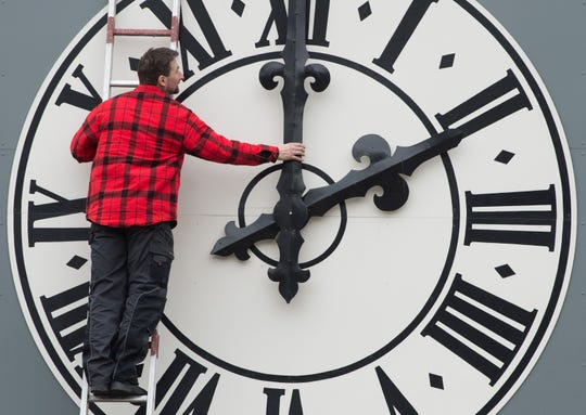 Picture taken on March 23, 2018 shows a technician working on the clock of the Lukaskirche Church in Dresden, eastern Germany.