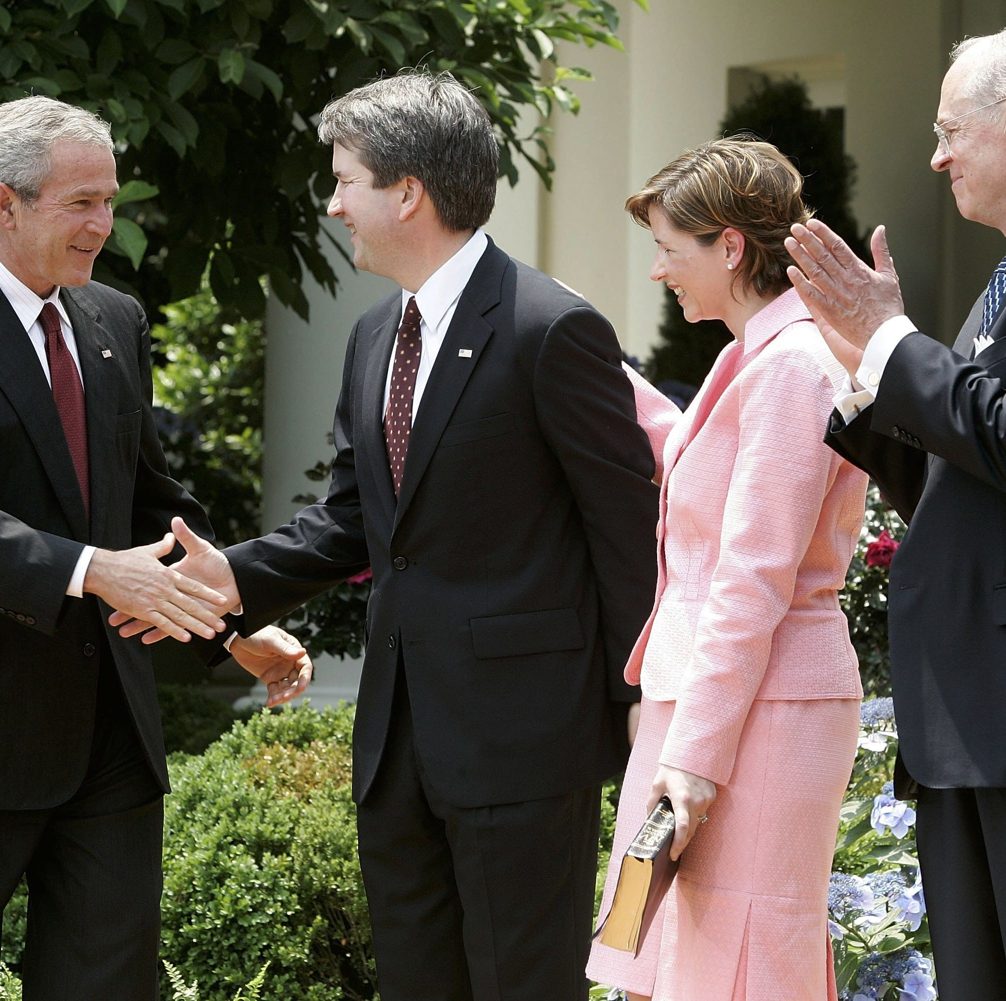 Brett Kavanaugh shakes hands with President George W. Bush after being sworn in by Supreme Court Justice Anthony Kennedy to be a judge on the U.S. Court of Appeals for the District of Columbia Circuit. His wife, Ashley, looks on.