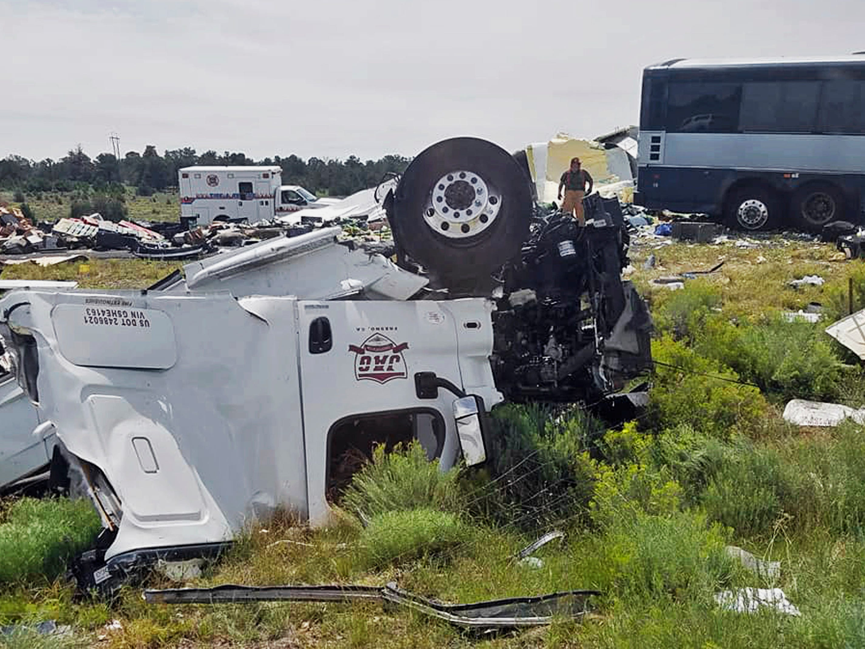 First responders work the scene of a collision between a Greyhound passenger bus and a semi-truck on Interstate 40 near the town of Thoreau, N.M., near the Arizona border on Aug. 30, 2018. Multiple people were killed and others were seriously injured. Officers and rescue workers were on scene but did not provide details about how many people were killed or injured, or what caused the crash.