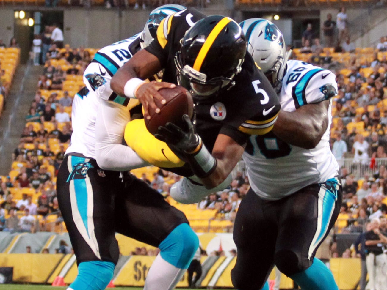 Pittsburgh Steelers quarterback Joshua Dobbs dives between Carolina Panthers defensive back Rashaan Gaulden (28) and defensive tackle Tracy Sprinkle (68) for a touchdown during the first quarter at Heinz Field.