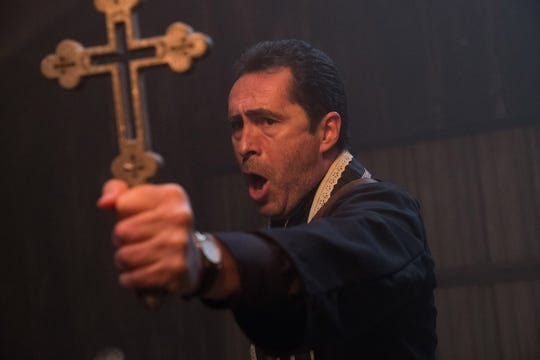 "Father Burke (Demian Bichir) uses a crucifix to ward off evil in ""The Nun."""