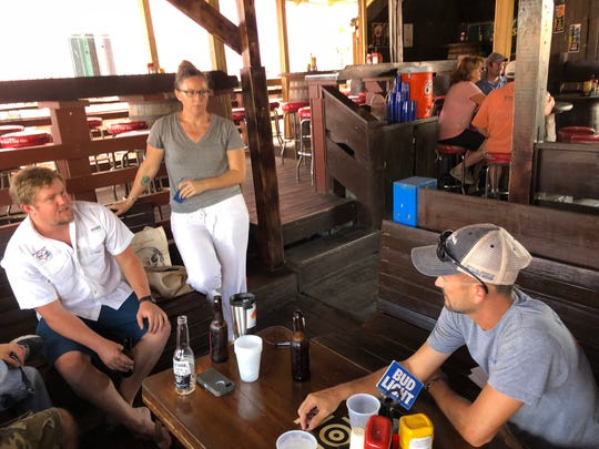 Connor Masterson, left, Meaghan Enright, and Jeff Quinlan, who run non-profit foundations for St. John recovery, plan upcoming projects at a bar in Cruz Bay.