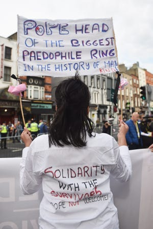 A protester holds up a sign in reference to the sex abuse scandal within the Catholic Church when Pope Francis travels through the city in the Popemobile on August 25, 2018 in Dublin, Ireland.