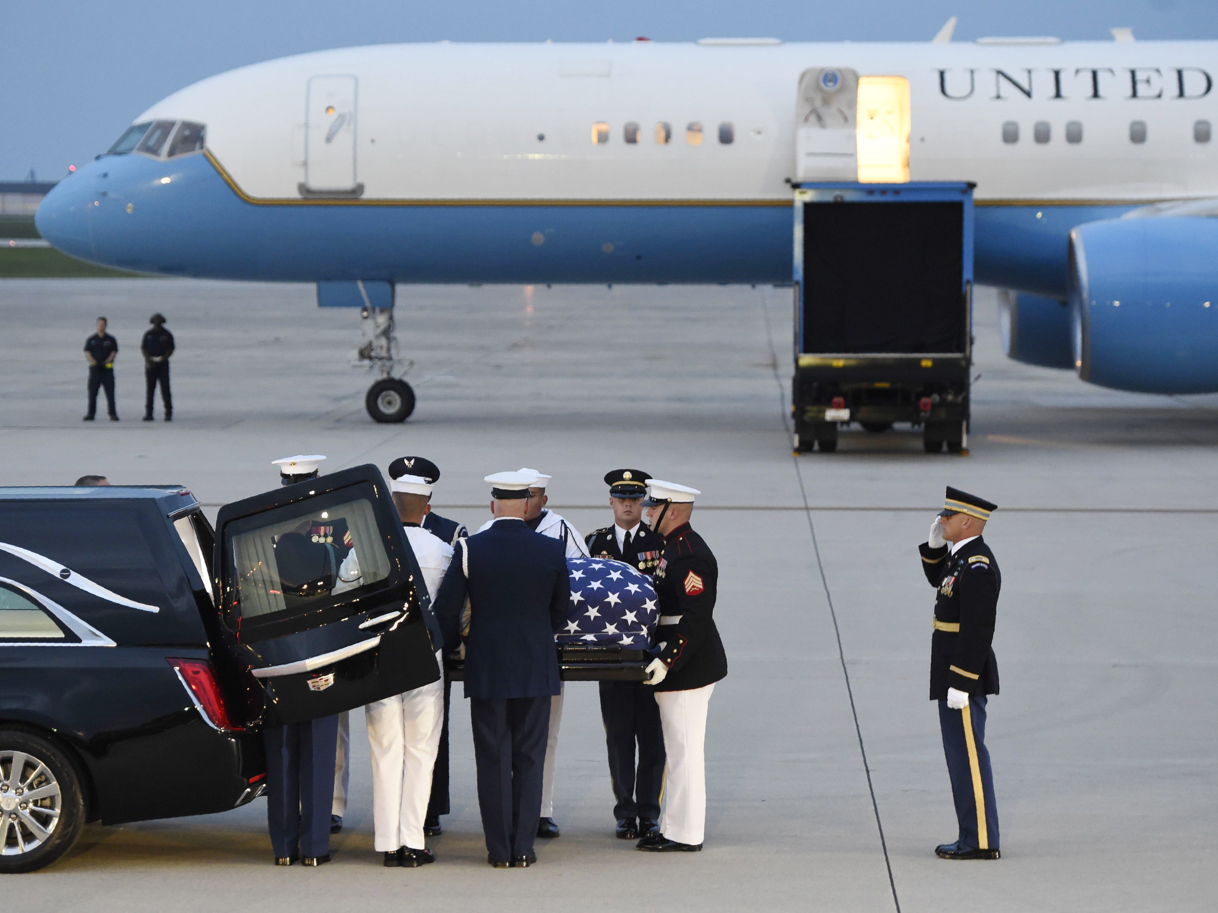 Members of the military carry the flag-draped casket of the late US Senator John McCain, Republican of Arizona, after arriving on a military airplane at Joint Base Andrews in Maryland, August 30, 2018. (Photo by SAUL LOEB / AFP)SAUL LOEB/AFP/Getty Images ORG XMIT: Senator J ORIG FILE ID: AFP_18Q463