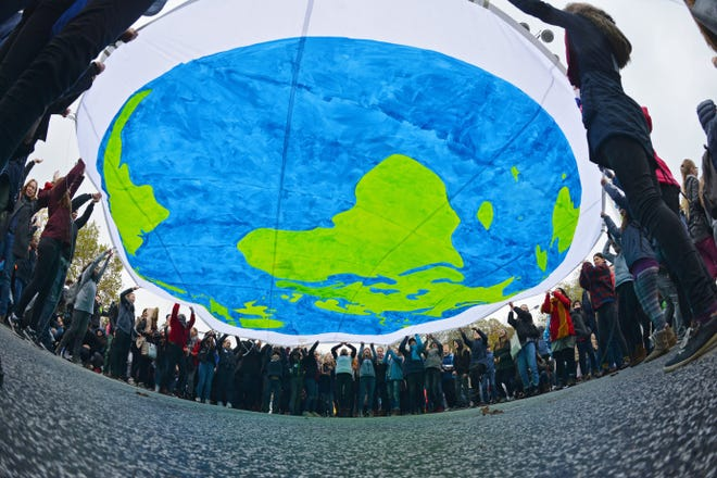Protesters hold a banner depicting the earth on the opening day of the UN Climate Change Conference COP23, in Bonn, Germany, on Nov. 6, 2017.