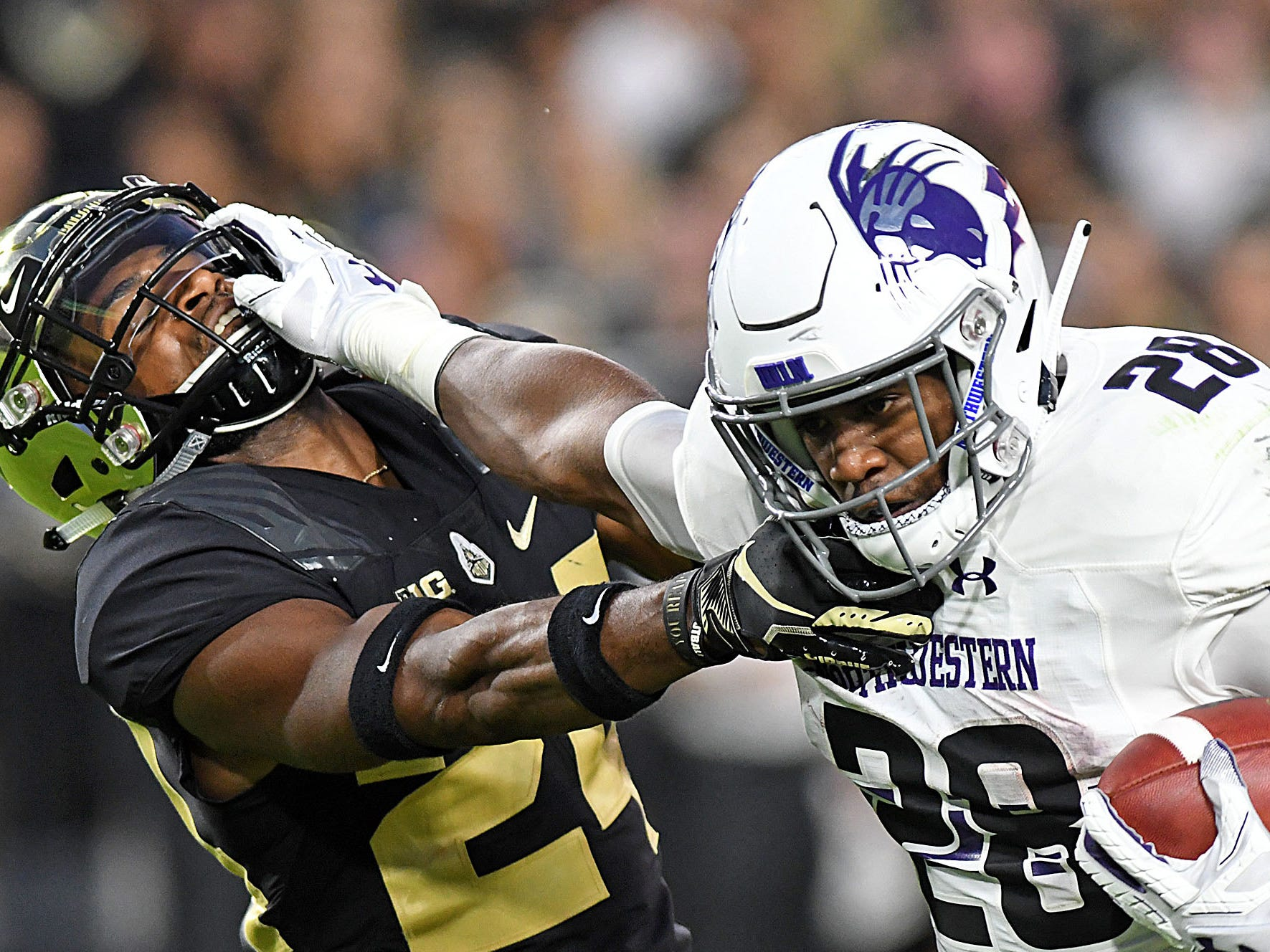 Northwestern running back Jeremy Larkin stiff arms  Purdue cornerback Tim Carson in the first half at Ross-Ade Stadium.