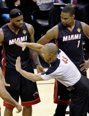 Referee Dan Crawford (43) calls Miami Heat forward LeBron James, left, with a technical foul as center Chris Bosh looks on during the second half in Game 2 of the NBA basketball finals on Sunday, June 8, 2014, in San Antonio.
