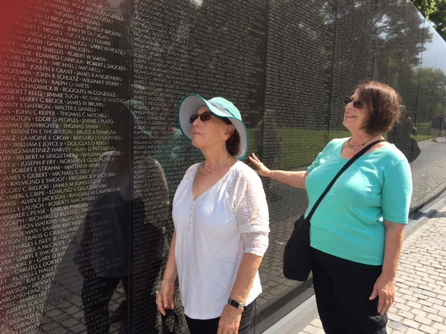 Sue Halfond and her cousin, Lois Richards, visit the Vietnam Veterans Memorial Friday.
