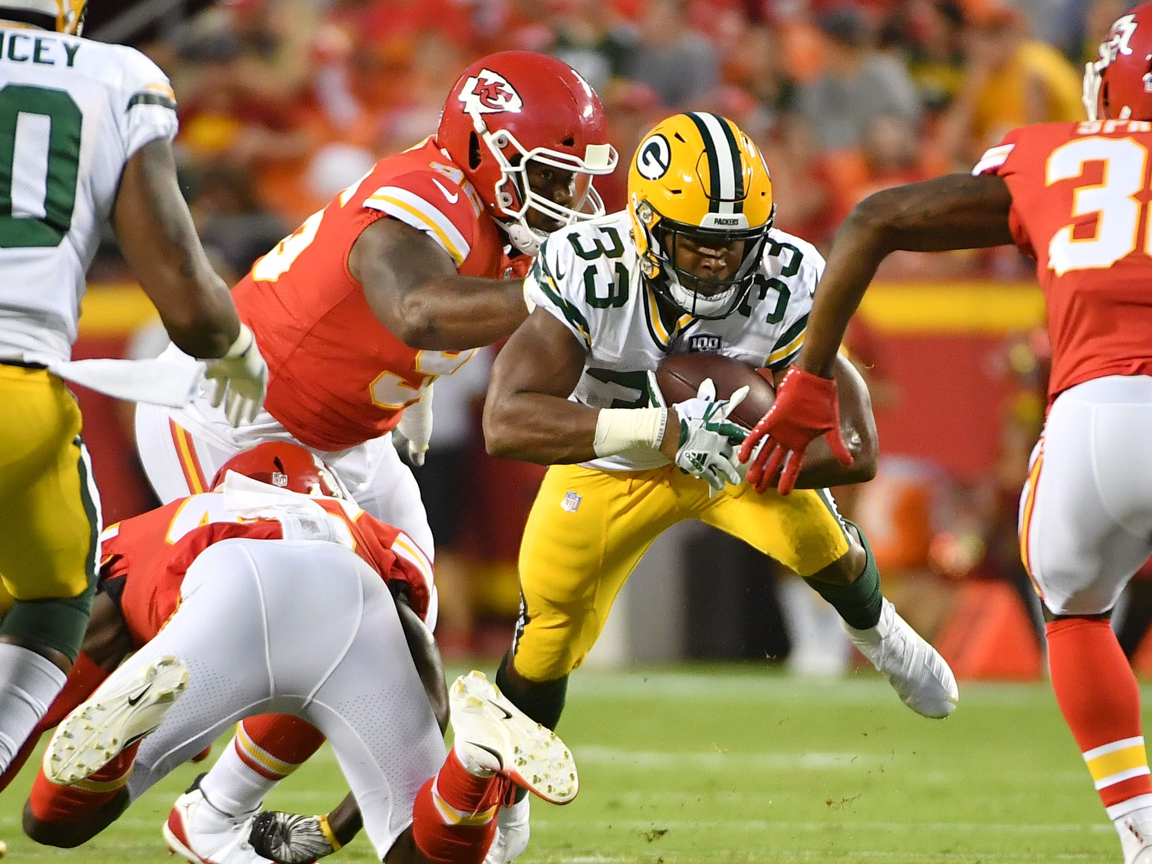 Green Bay Packers running back Aaron Jones runs the ball and is tackled by Kansas City Chiefs defensive back Leon III McQuay (34) during the first half at Arrowhead Stadium.