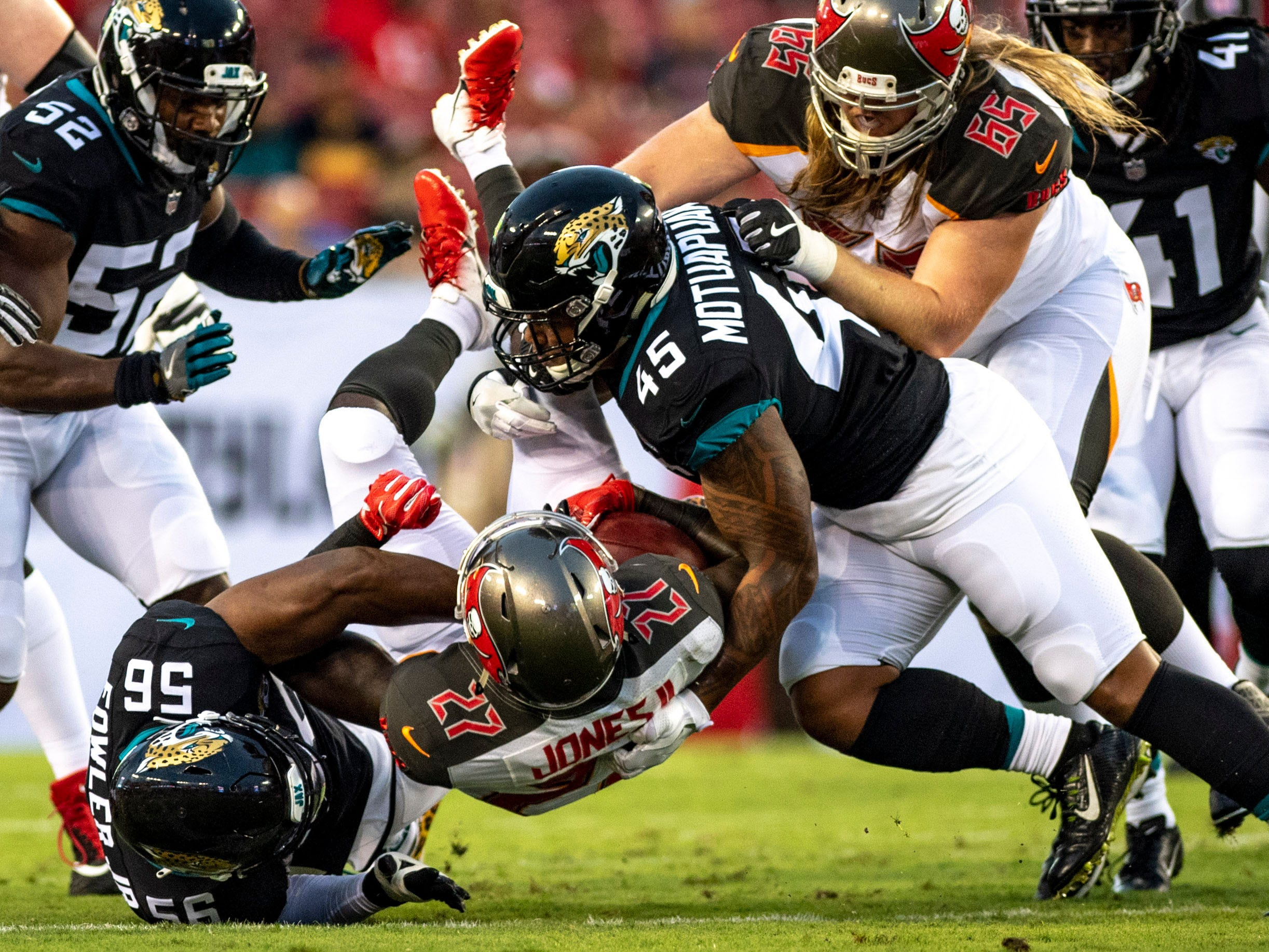 Tampa Bay Buccaneers running back Ronald Jones is tackled after running the ball by Jacksonville Jaguars defensive end Dante Fowler Jr. (56) and linebacker Andrew Motuapuaka (45) during the first half at Raymond James Stadium.