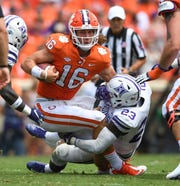 Furman inside linebacker Elijah McKoy (23) brings down Clemson quarterback Trevor Lawrence (16) during the 2nd quarter Saturday, September 1, 2018 at Clemson's Memorial Stadium.