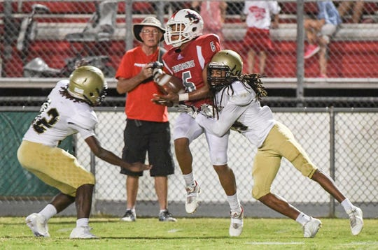 Palmetto junior Landon Owens catches a ball near Pendleton senior Antwin Jackson, left, during the second quarter at Palmetto High School in Williamston on Friday, August 24, 2018.
