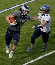 Menasha's Riley Zirpel stiff arms Xavier's Sam Loken during a game at Calder Stadium in Menasha.