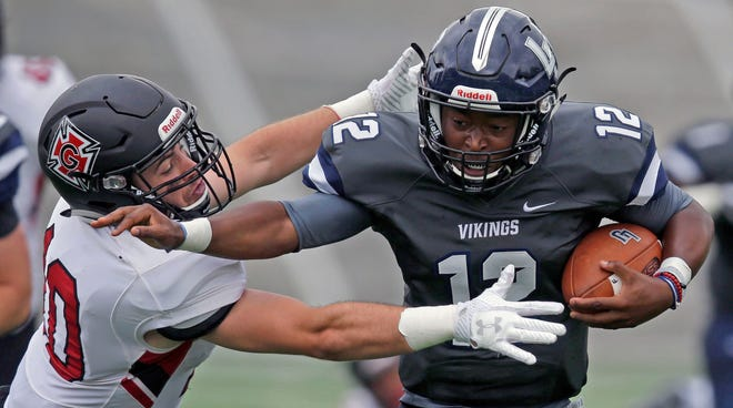 Quarterback D'Andre Weaver of Lawrence University carries the ball while being pursued by Vinny Pavoni of Grinnell College on Saturday on Ron Roberts Field at the Banta Bowl in Appleton.