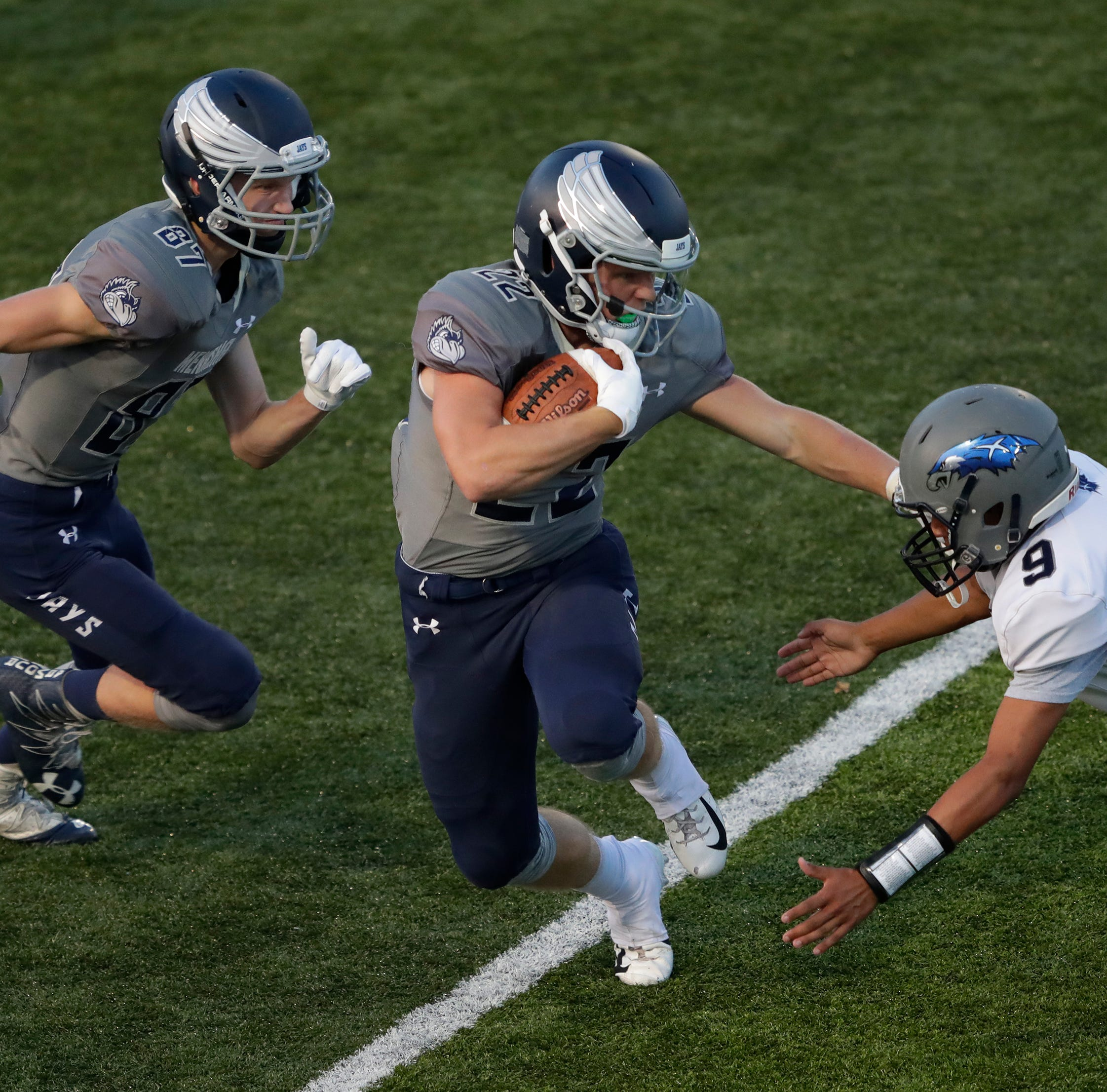 Menasha High School's Tyler Roehl (22) stiff arms Xavier High School's Frankie Rasmus (9) for a gain during their football game Friday, August 31, 2018, at Calder Stadium in Menasha, Wis. 