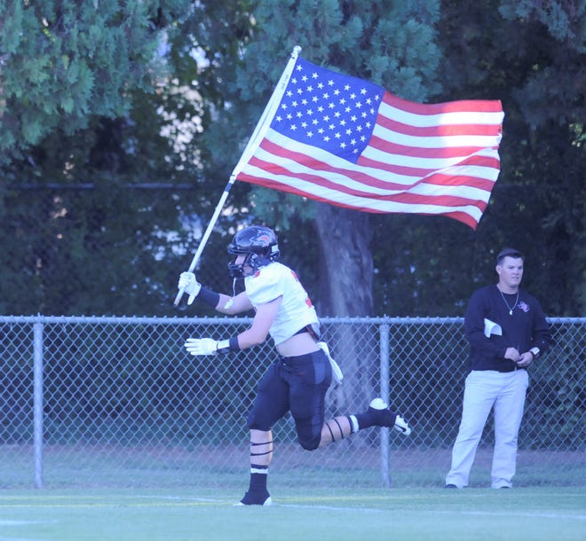 Colorado City's Reid Harris holds the US flag as he enters the field at Robert Nail Memorial Stadium in Albany on Aug. 31, 2018.