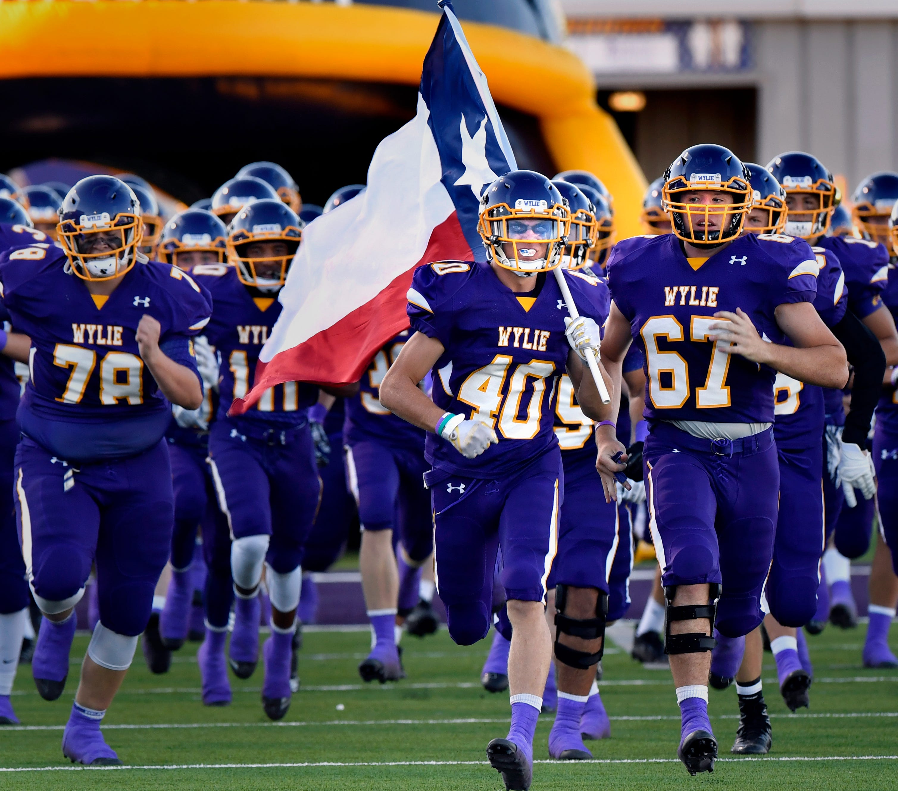 Wylie's Brazos Ham carries the Texas flag as he and the other Bulldogs take the field for their season opener Friday August 31, 2018 against Georgetown. Final score was 31-7, Georgetown.