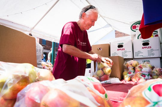 Rick Hall, of Justus Orchard, bags Honey Crisp Apples at the 72nd annual North Carolina Apple Festival in Hendersonville Saturday, September 1, 2018.