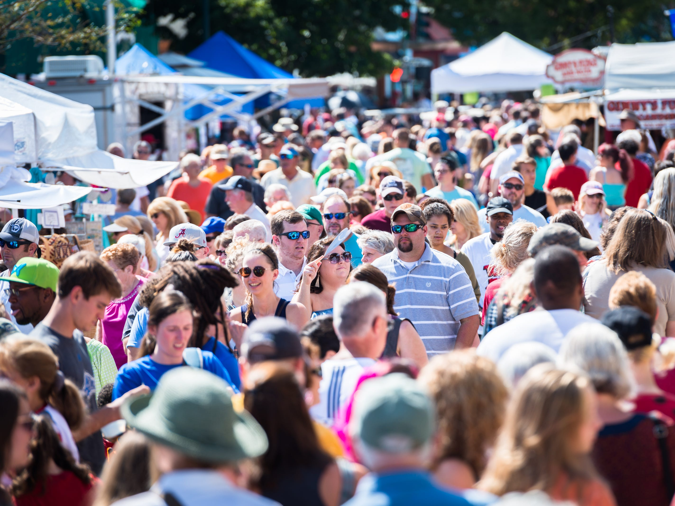 Attendees of the 72nd annual North Carolina Apple Festival in Hendersonville walk down Main Street past vendors Saturday, September 1, 2018.
