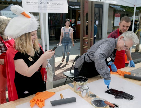 Hilary Michaels, left, wears a goose hat as she watches artist Lynda Sherman get the ink ready for printing at the Wayzgoose Arts Festival at Fourth Street and Pacific in downtown Bremerton on Saturday, September 1, 2018.