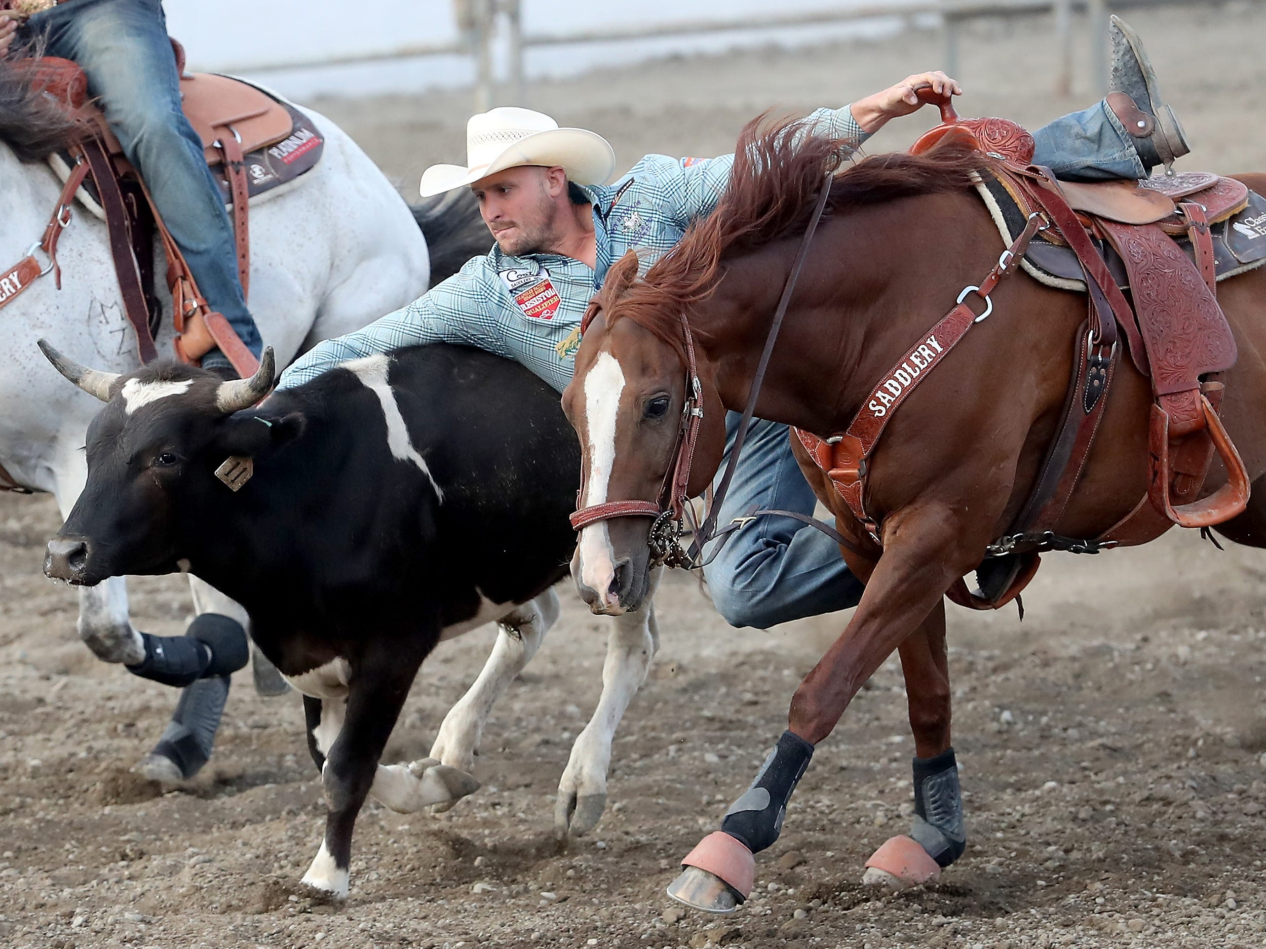 Steer wrestler Kyle Irwin, of Roberstdale, AL, dismounts and grabs the steer at the Kitsap County Fair & Stampede on Thursday, August 23. 2018.