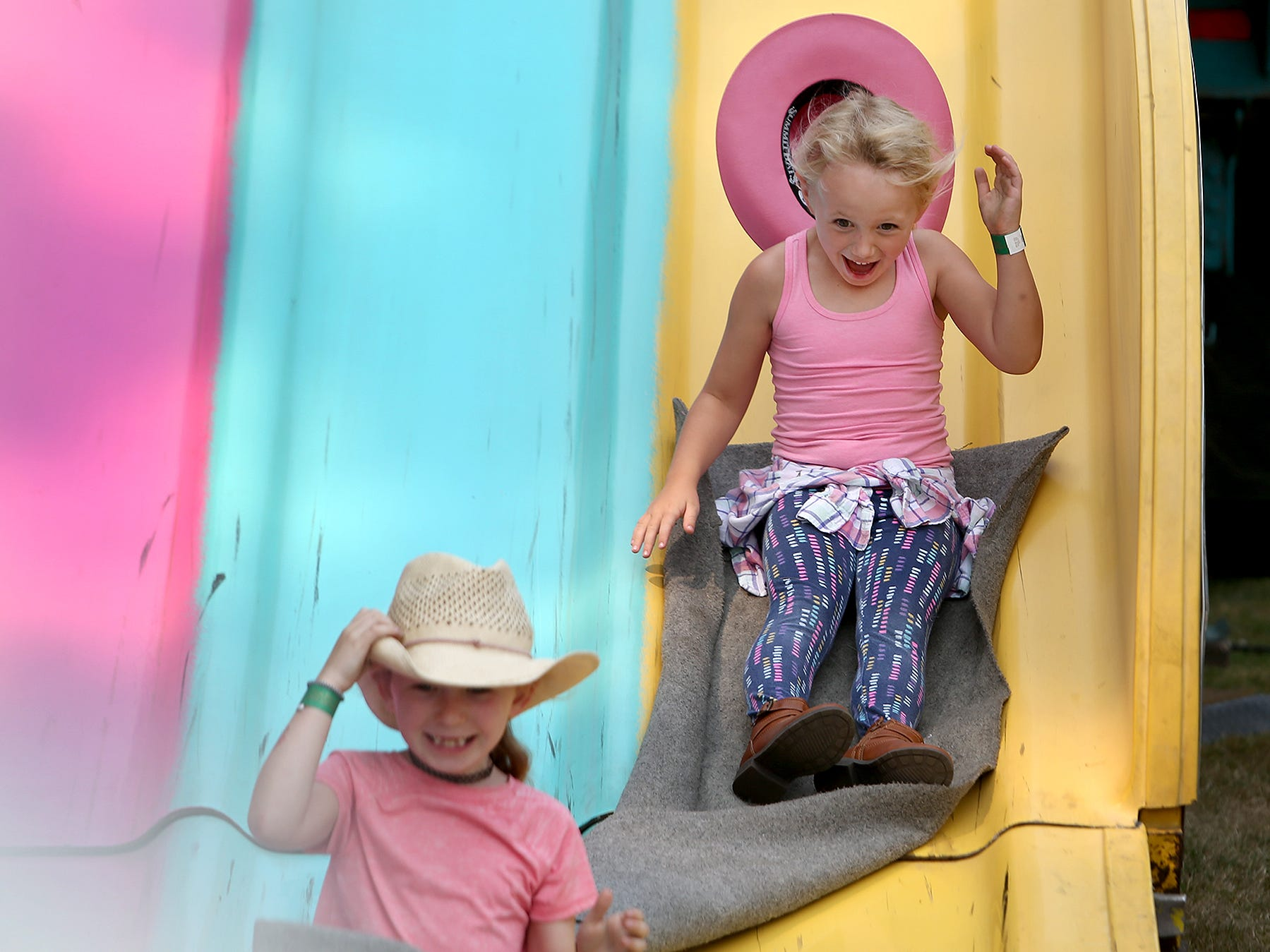 Sammie Shields, 6, of Bremerton, loses her cowgirl hat going down the slide at the Kitsap County Fair & Stampede opening day on Wednesday, August 22, 2018.On the left is her friend Della Russell, 7, of Bremerton.