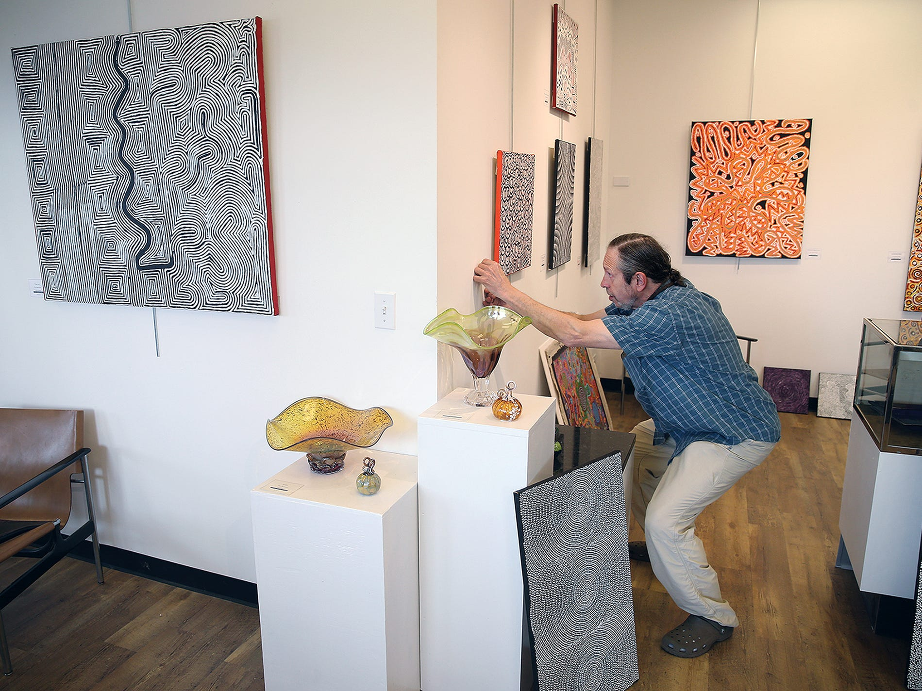 Jeffrey Moose lines up a painting to hang in his gallery located on Bainbridge Island's Winslow Way. He specializes in aboriginal Australian art.