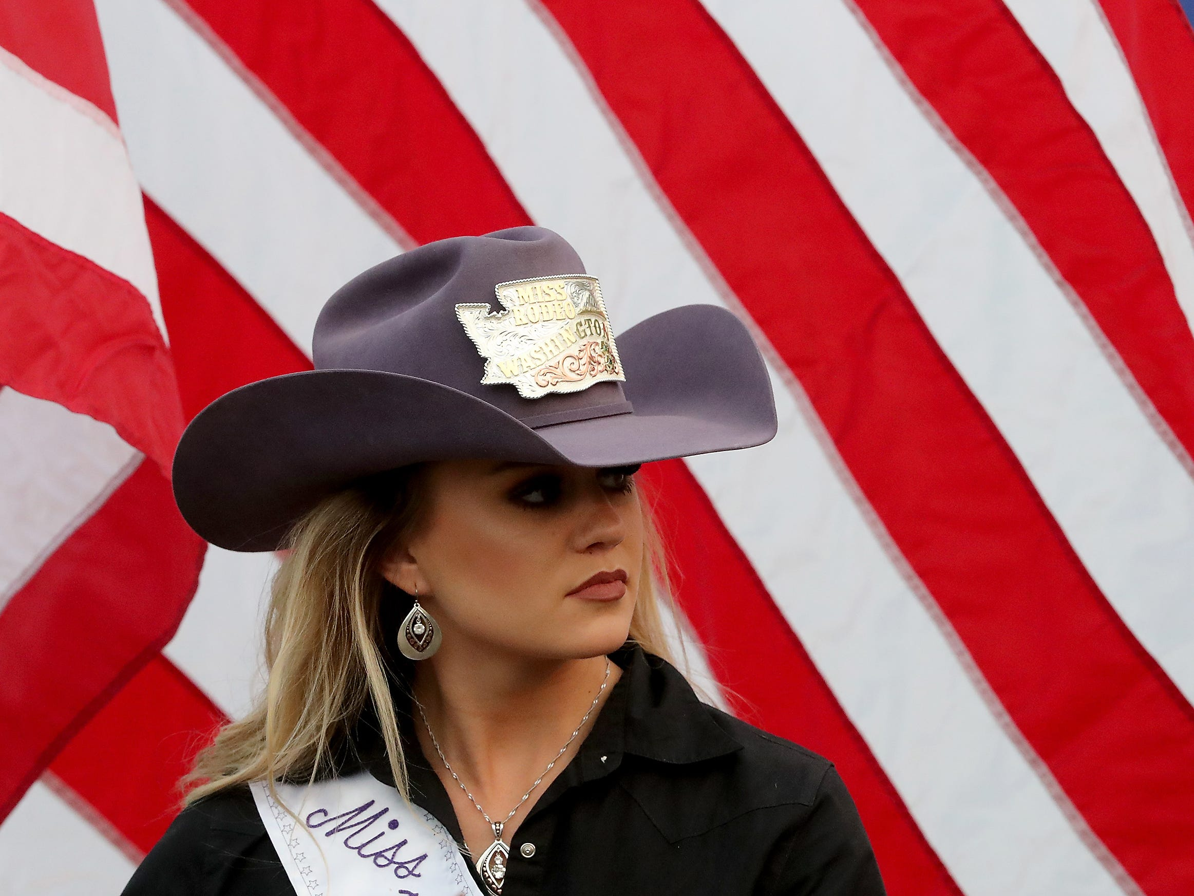 MIss Rodeo Washington Beth Snider carries the American flag into the arena prior to the start of the PRCA Xtreme Bulls event at the Kitsap County Fair & Stampede on Wednesday, August 22. 2018.