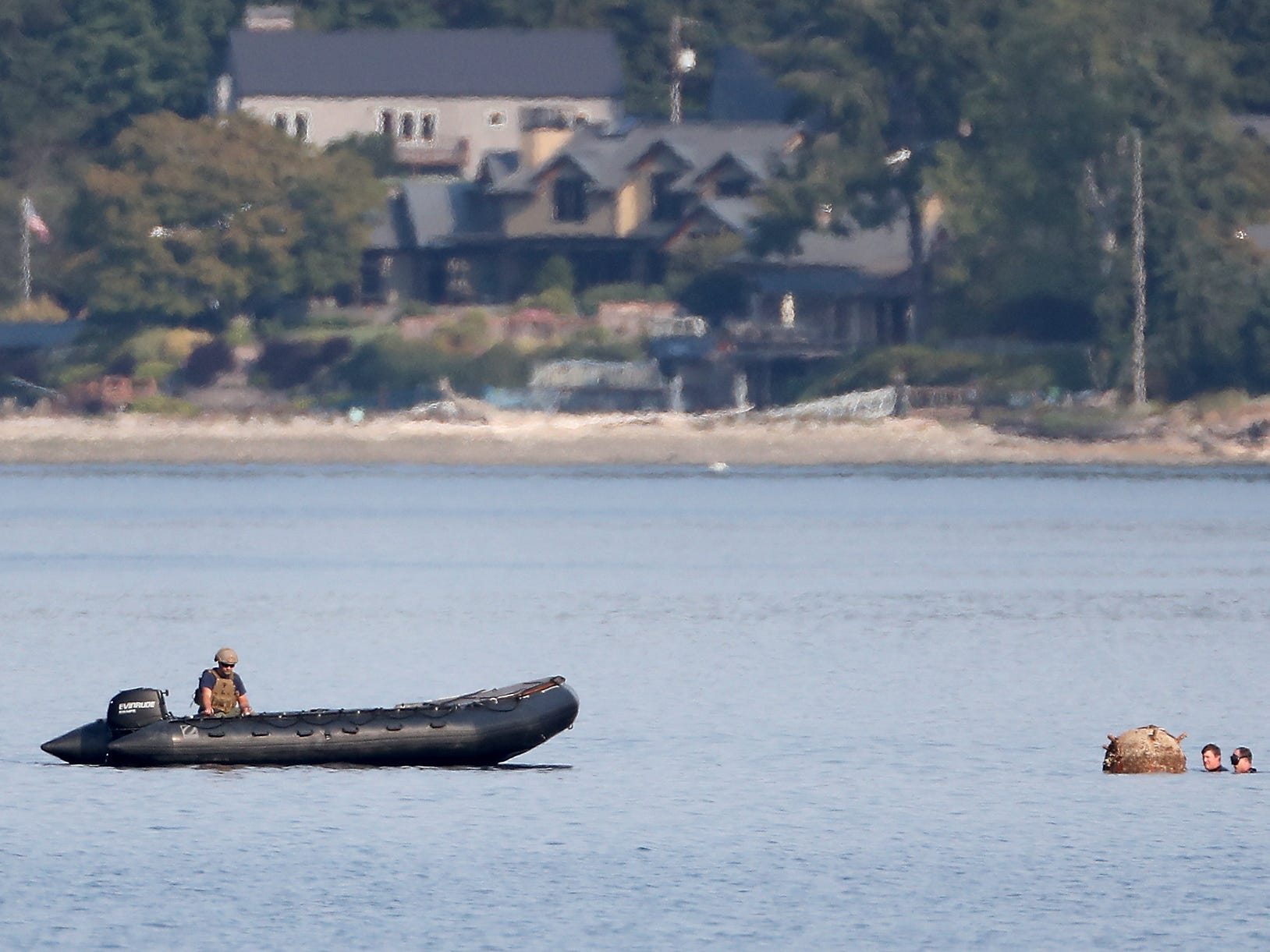 """A pair of US Navy divers attach a rope to a """"reported unexploded ordnance"""" drifting in the water between Brownsville Marina and Bainbridge Island, Washington on Tuesday, August 28, 2018. (AP Photo / Meegan M. Reid, Kitsap Sun)"""