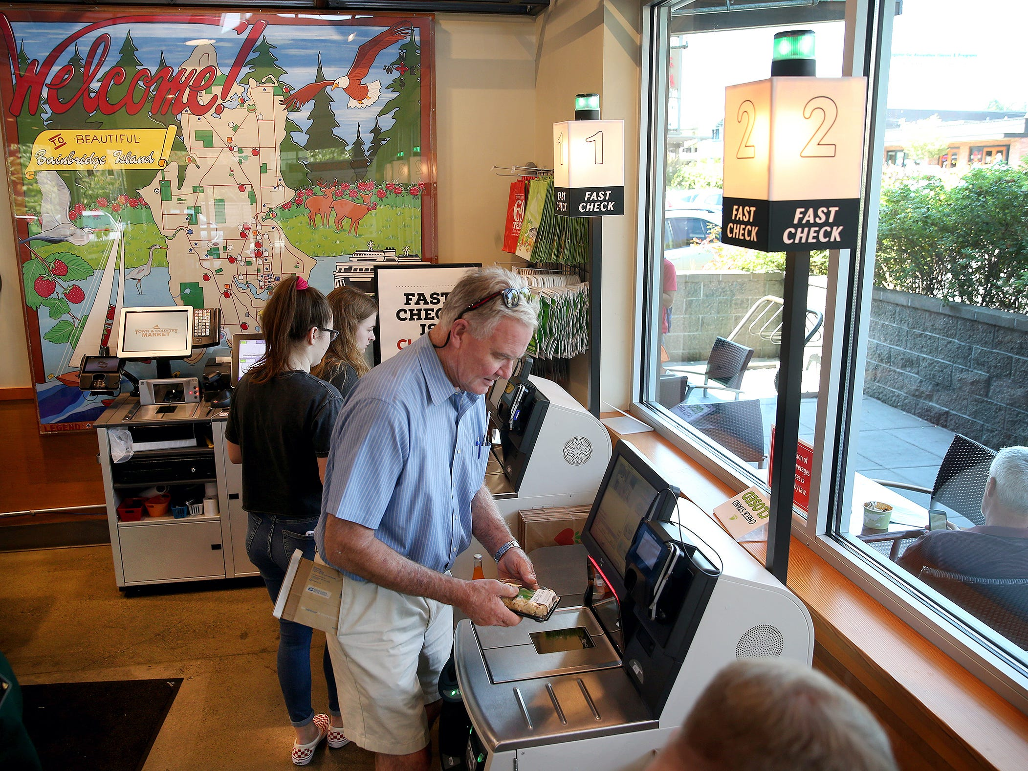 Craig Clark, of Bainbridge, uses the new-self checkout station at the Town & County Markets on Bainbridge Island to pay for his sushi.
