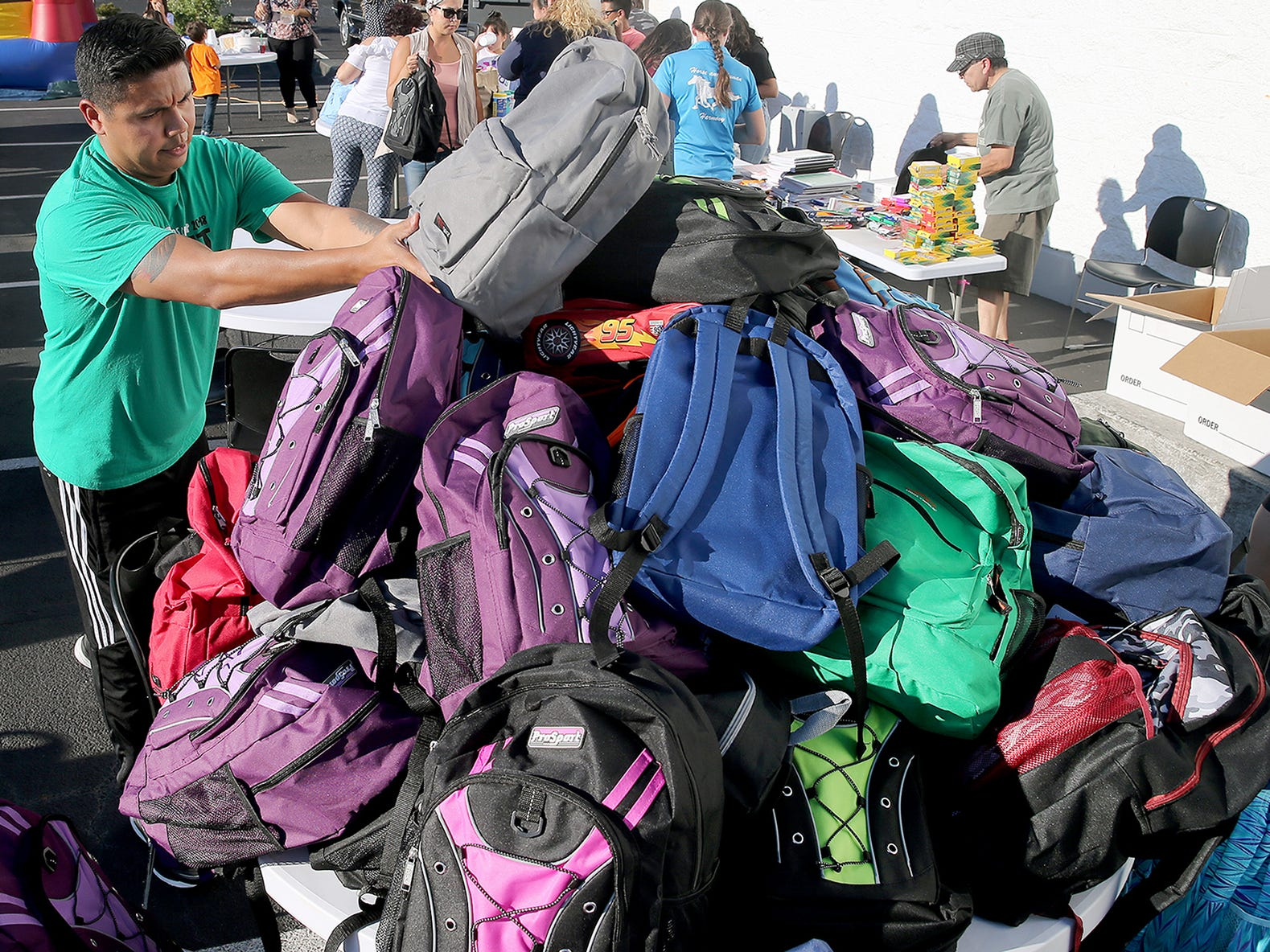 """Rene Tovar makes a mountain of backpacks full of school supplies for children at the Newlife training Center in Silverdale on Monday, August 27, 2018. Newlife church has been trying to build bridges to the Spanish-speaking community. After the popularity of """"Spanish night"""" at its summer camp in July."""