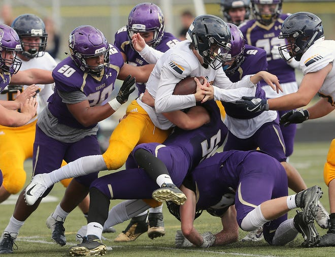 Bainbridge quarterback Gannon Winkler (center) is stopped by the North Kitsap defense (clockwise from left) of Isaiah Kahana, Cameron Pelegri, Colton Bower, Kyle Green and Cache Holmes on Saturday, September 1, 2018.