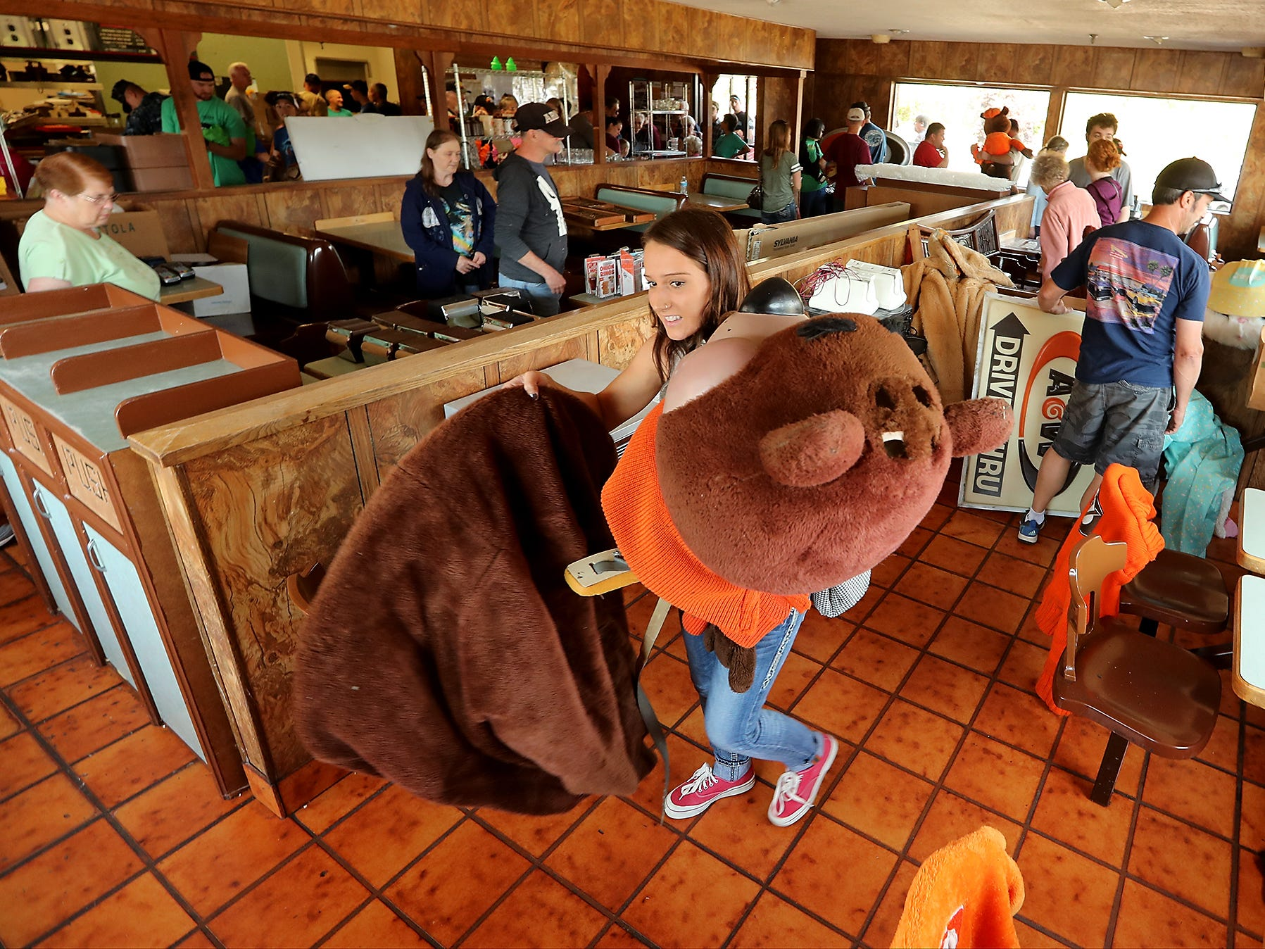 Melanie Zaccagnini, of Olalla, carries a Great Root Bear (also called Rooty who is the mascot for A&W Root Beer) costume do the checkout area during a sports memorabilia giveaway and restaurant equipment sale at the A&W in Port Orchard on Wednesday, August 29, 2018.