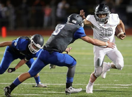 Central Kitsap's Alex Rifilong (30) stiff arms Olympic'sEzekiel Gillick (3) during the second half of the Battle of Bucklin Hill at Silverdale Stadium on Friday, August 31, 2018.