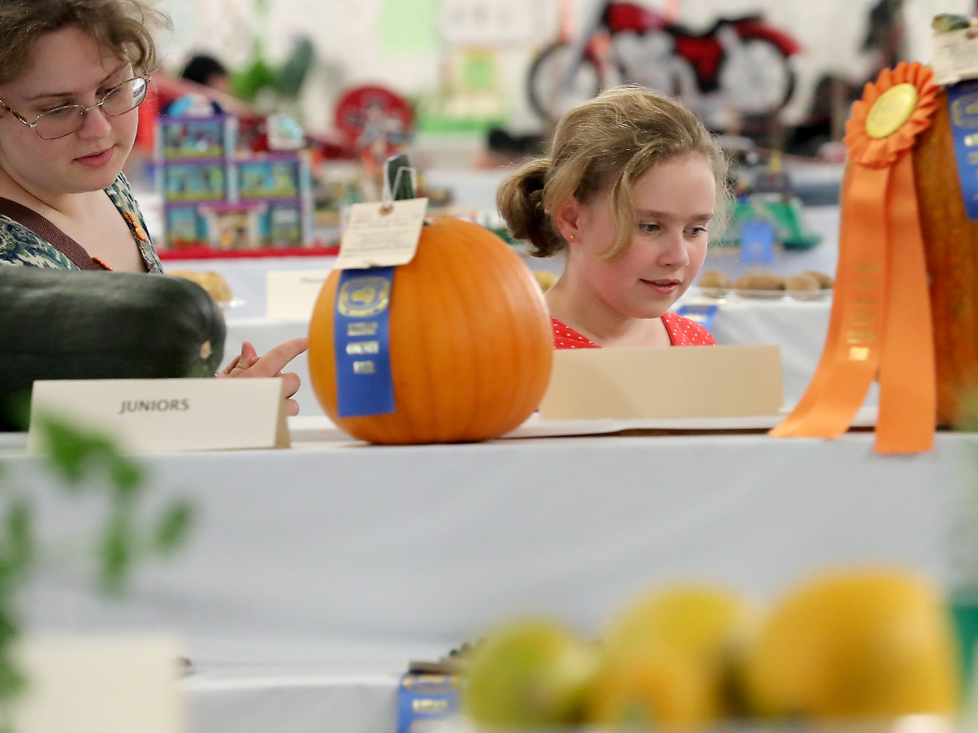Elizabeth Passage, 16, and sister Jennifer, 11, look over the tables of award winning vegetables during the opening day of the Kitsap County Fair & Stampede on Wednesday, August 22. 2018.